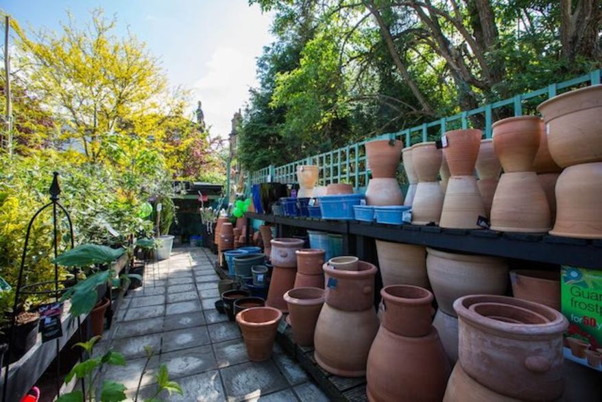 Two stacks of terracotta pots in the shade