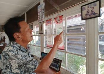 Drs Djomen Purba sedang menunjukkan foto penabalan Edwin Bingei Purba Siboro dengan istrinya boru Damanik. (foto : HTP)