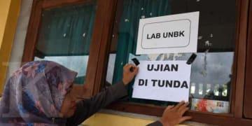 ILUSTRASI. Guru menempelkan famflet penundaan UNBK di SMK Negeri 1 Serang, Banten, Senin (16/3/2020).