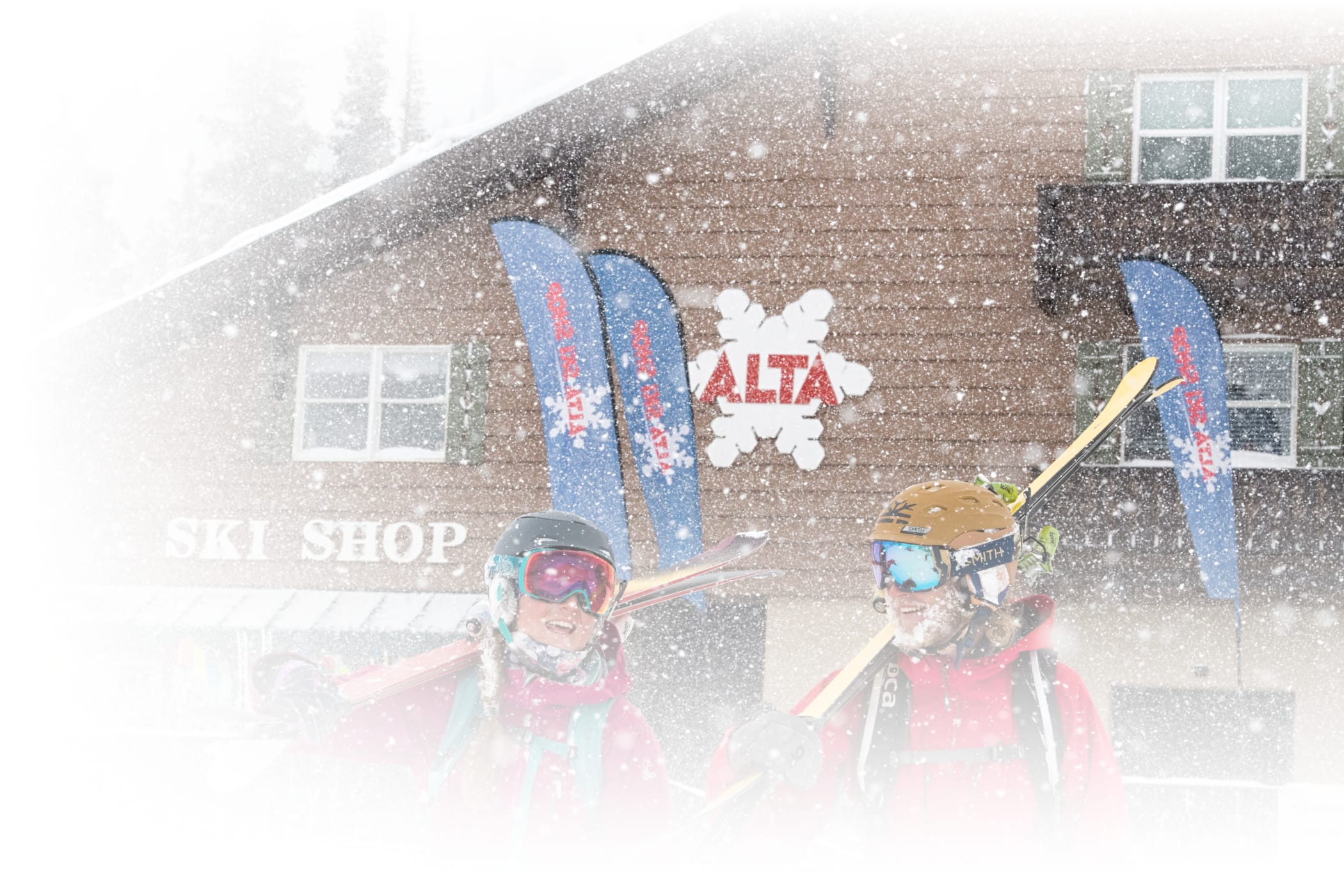Skiers carrying demo skis out of Alta's Ski Shop on snowy day