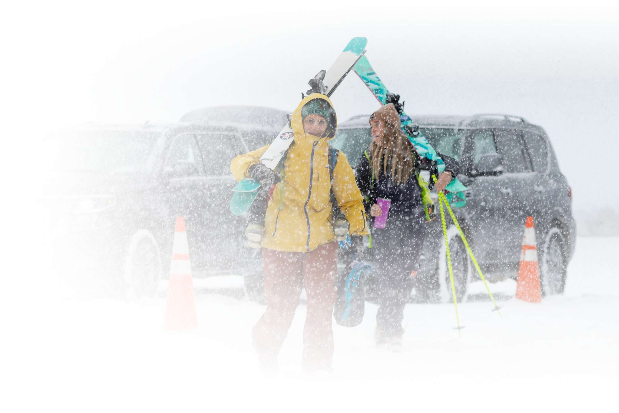 Skiers walk through the Wildcat parking lot on a snowy day at Alta Ski Area