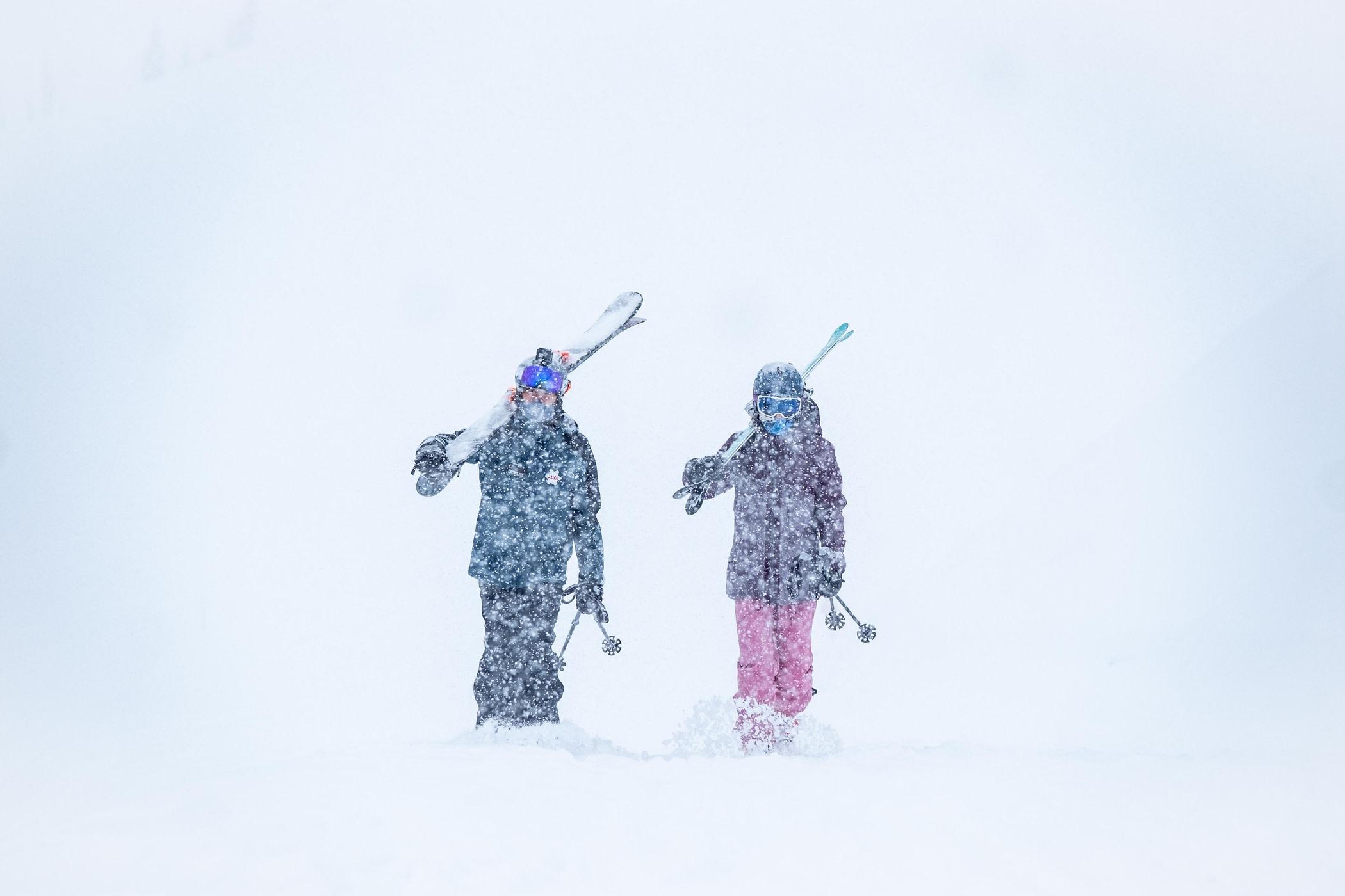 Skiers walking through a Saturday snowstorm at Alta
