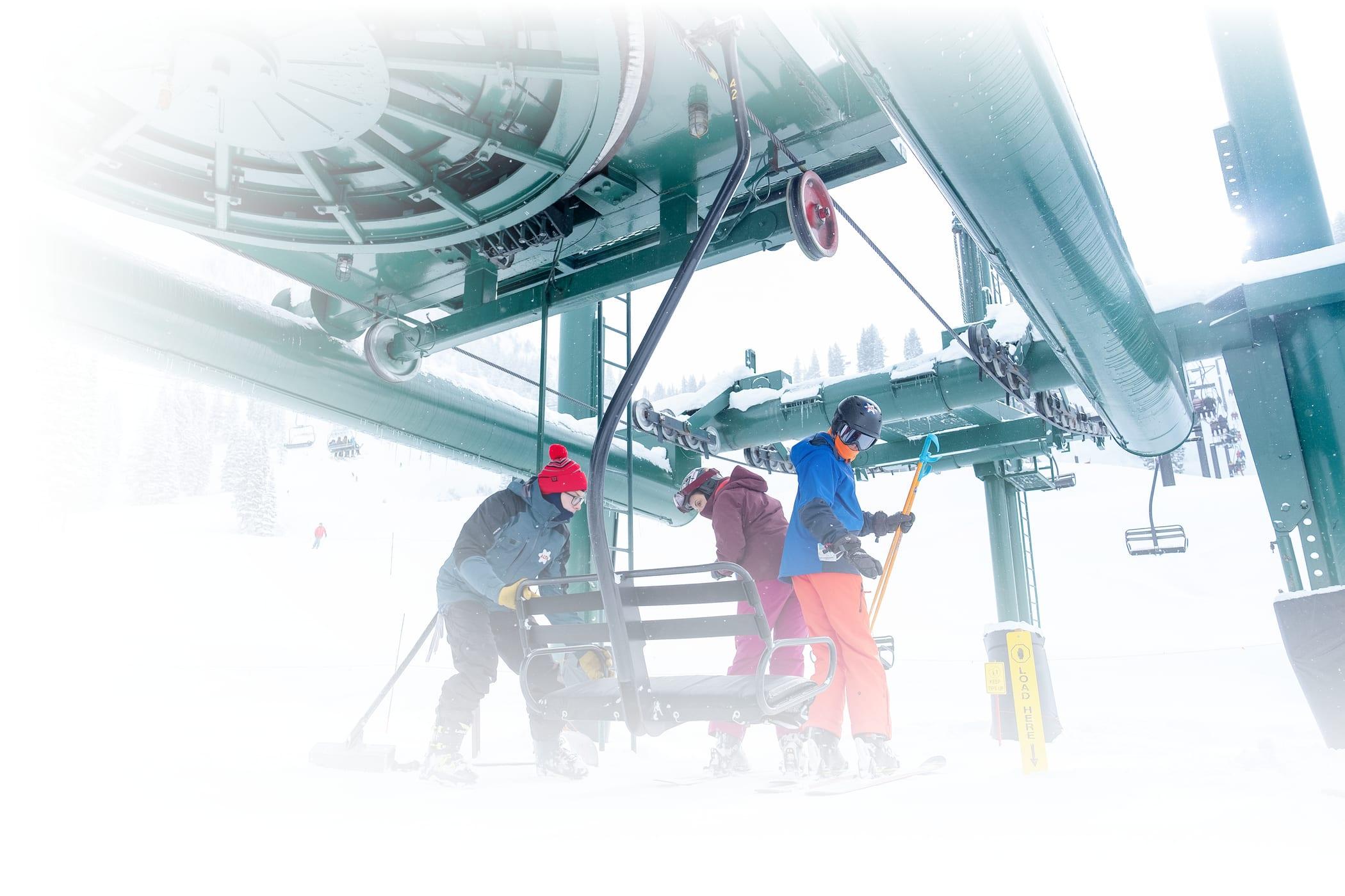 An Alta employee loads two skiers onto Wildcat lift