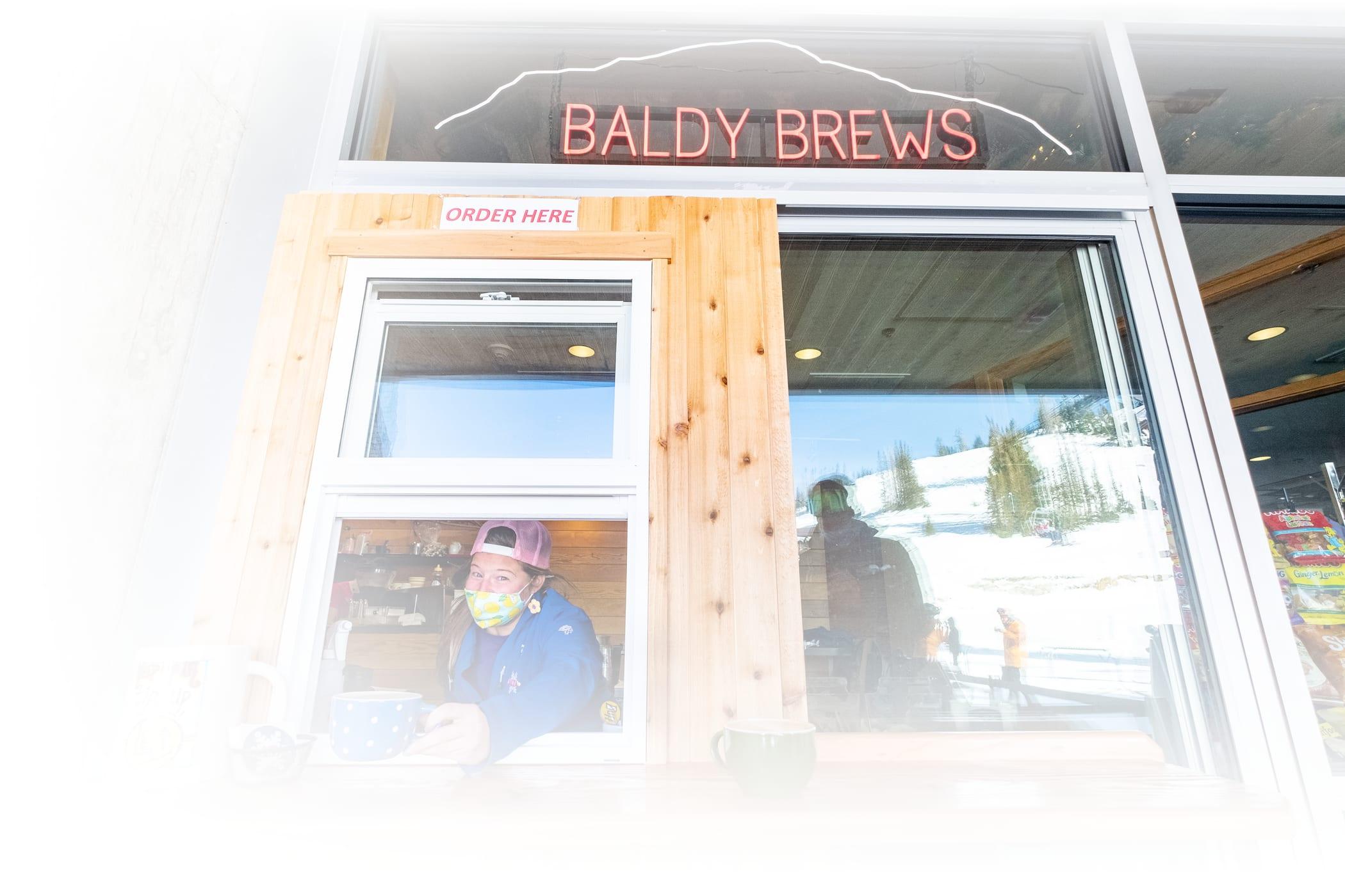 A Baldy Brews eployee serves a coffee through the new takeout window