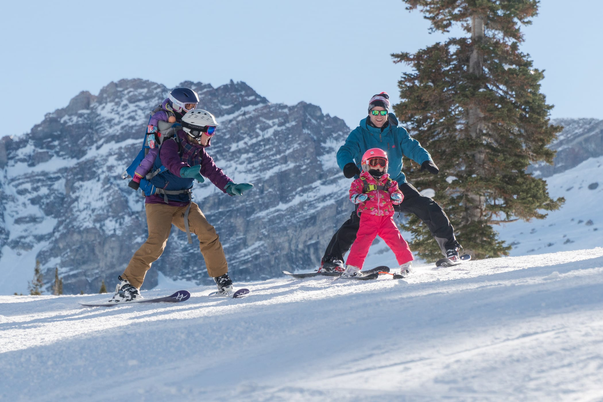 Mom with child in backpack, dad, and daughter skiing down slope