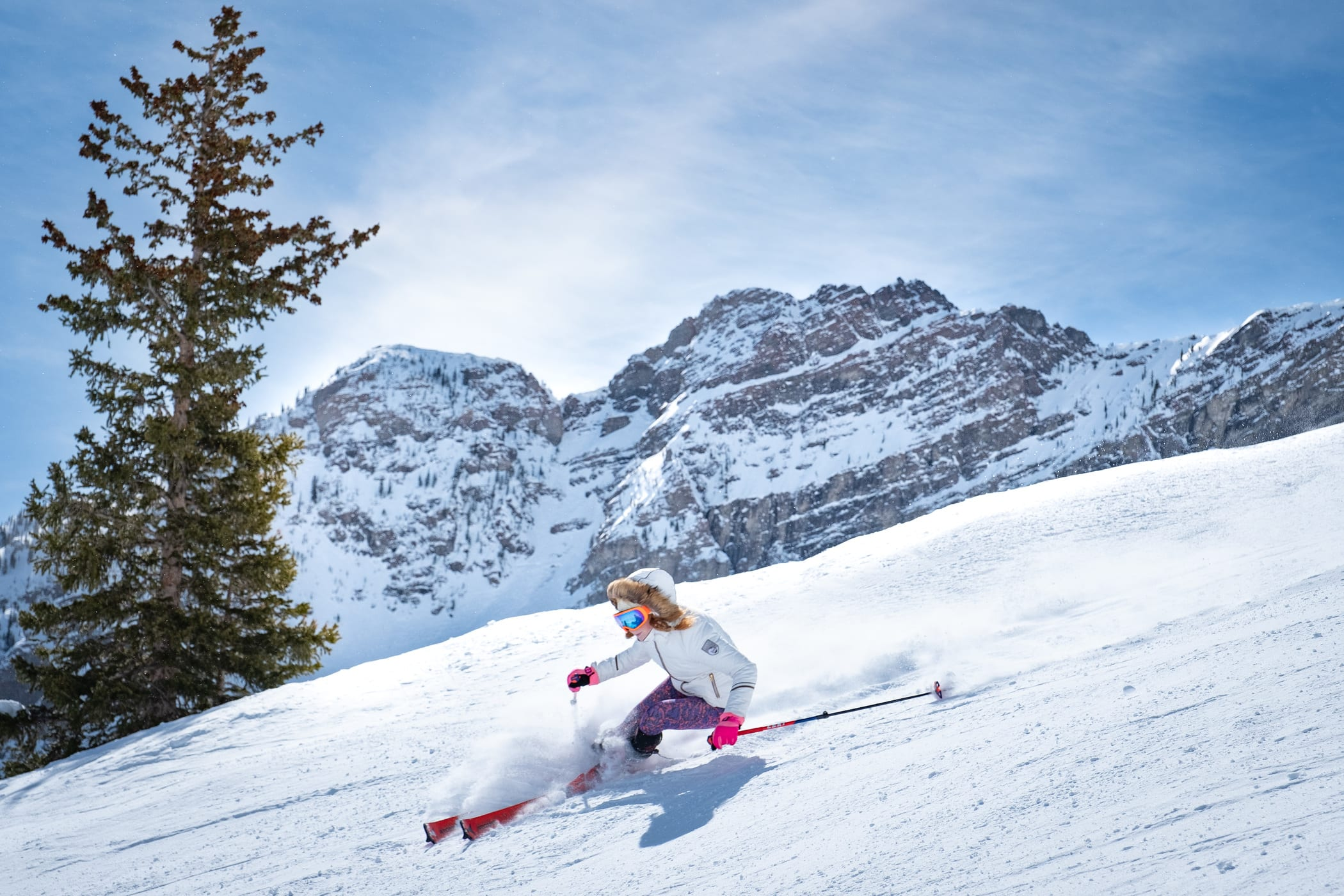 Girl with fur lined hood skiing moderate steep slope