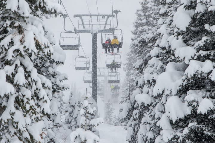 Skiers ride the Sunnyside lift in a snow storm