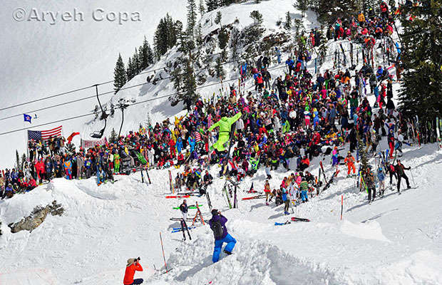 Skier jumping above a crowd of bright colored skiers with alta and American flag in background
