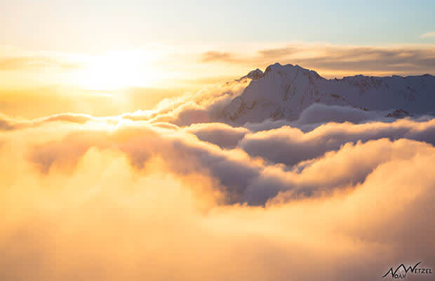 Mountain rising above thick clouds with amber sunset sky