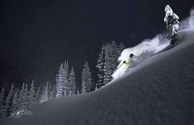 Skier illuminated skiing deep snow at night with clear starry sky