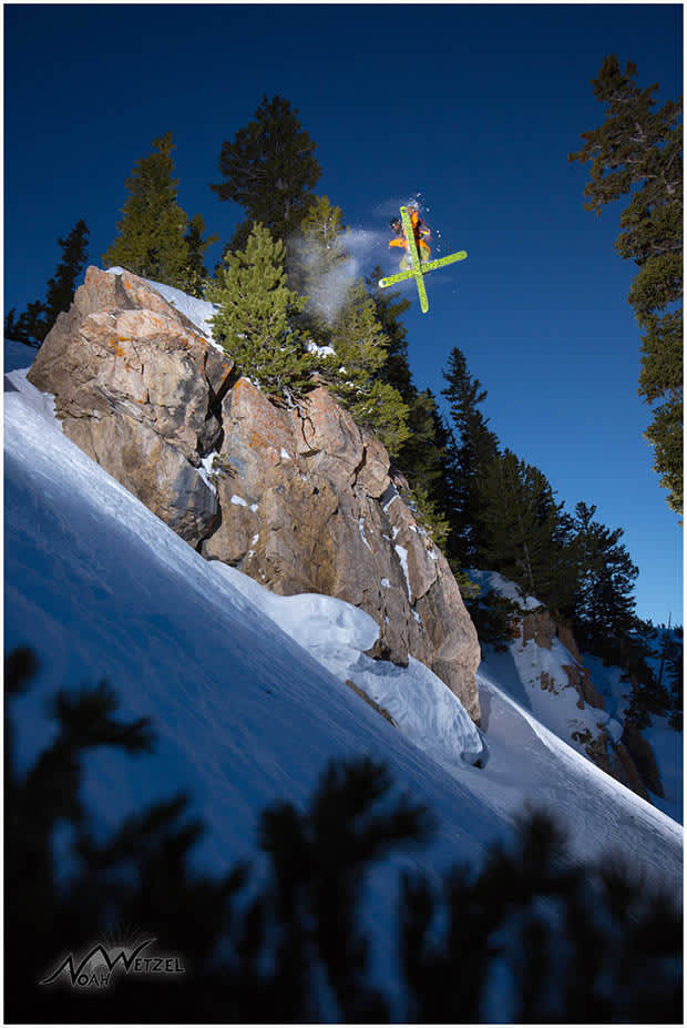 Skier jumping off clif face with fresh snow and clear blue sky