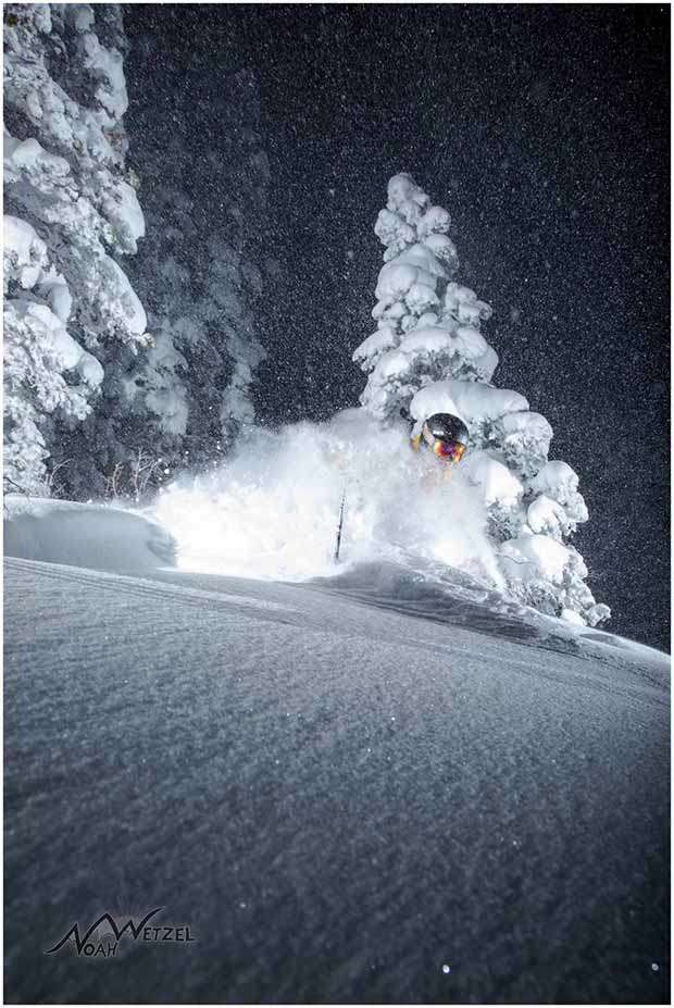 Skier skiing deep powder at night with clear starry skies