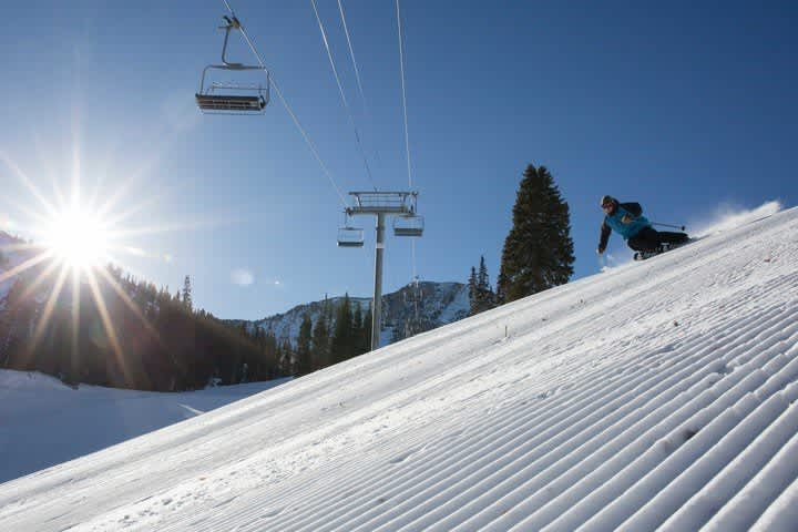 Skier laying down a right turn on fresh corduroy