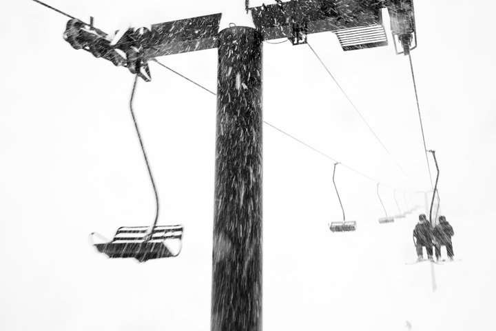 Skiers ride Wildcat lift in a blizzard
