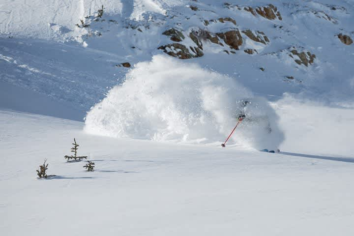 Skier hidden by cloud of snow, skiing deep fresh powder snow