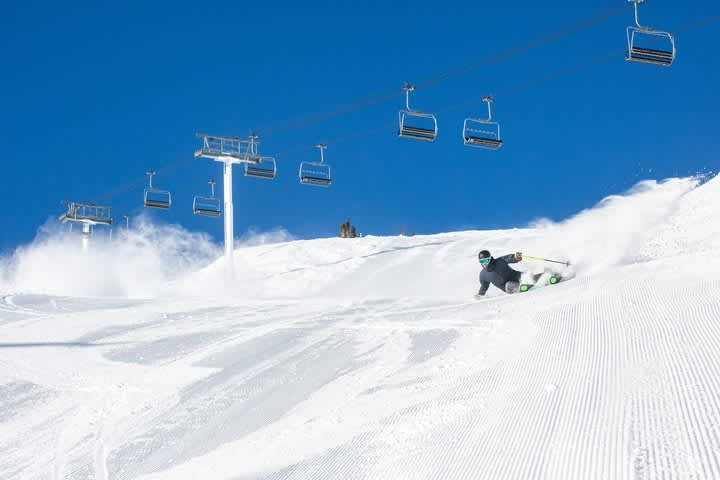 Skier making sharp turn on streep groomed slope