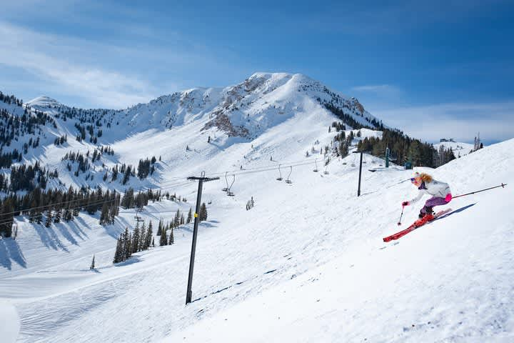 Skier makes left turn with Mt. Baldy behind