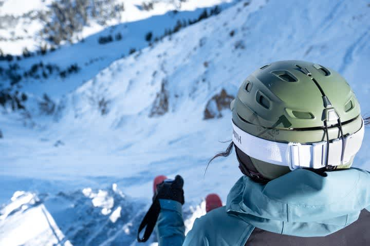 Woman with green helmet looking down steep ski run