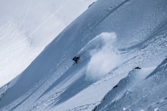 Skier, Megan McJames, skiing deep powder snow on steep slope