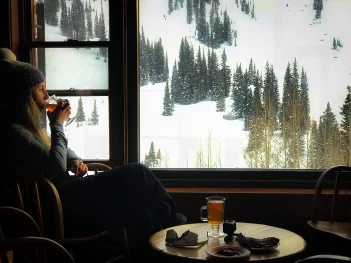 Skier enjoys Alta's apres scene with a nice drink over-looking the slopes