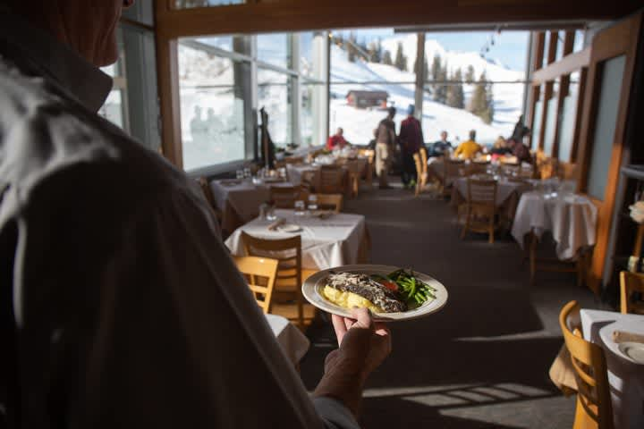 Waiter brings food to skiers at Collins' Grill