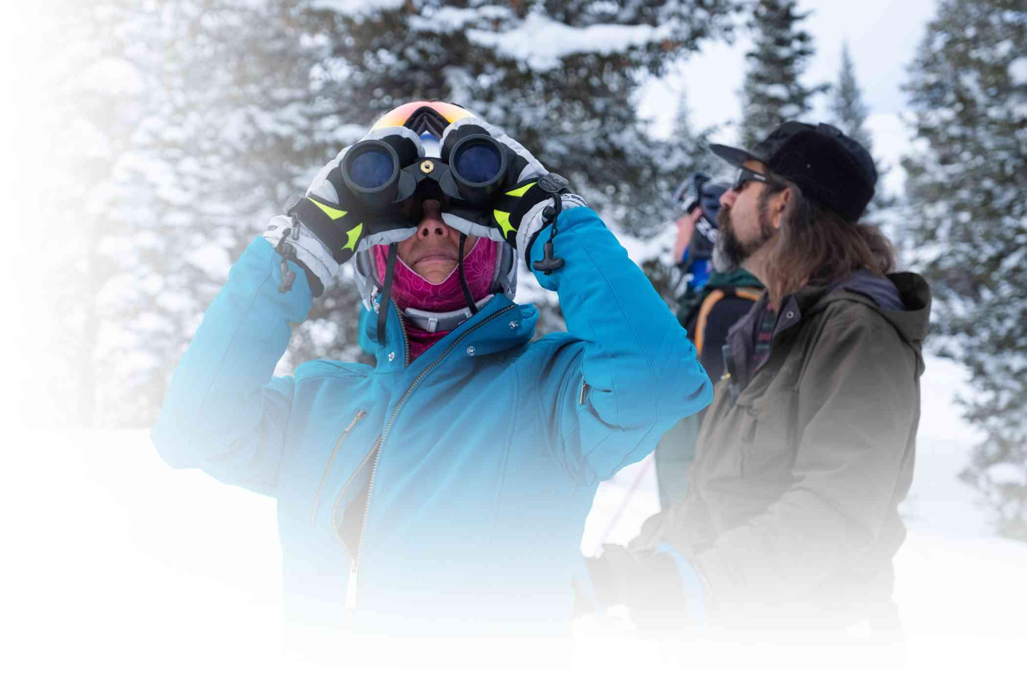 Woman looking through binoculars while birding on skis at Alta