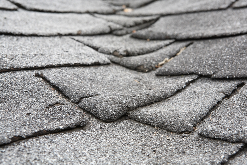 Warped shingles indicate the need for new roofing.