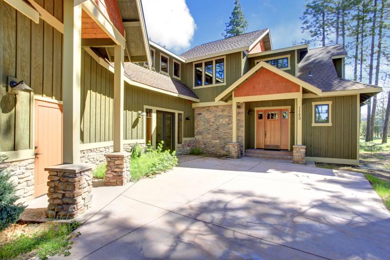 Exterior of house with siding and stone accent wall.