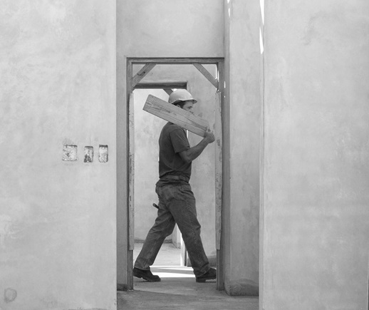 A man walking with a wooden plank on a construction site