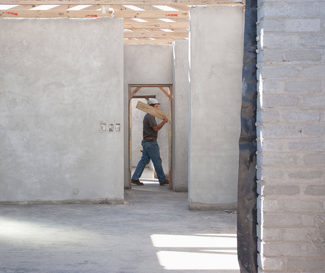 A man walking with a wooden plank in a construction site