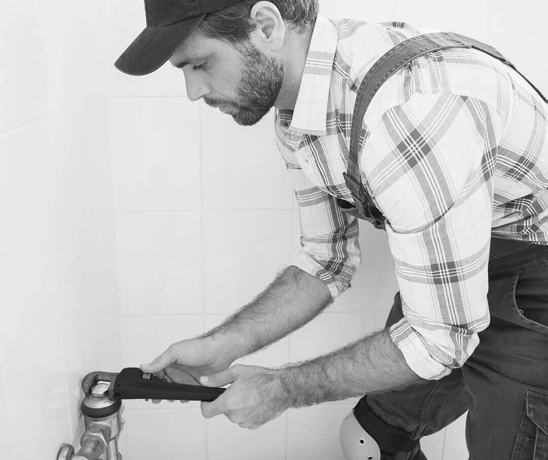 A plumber using a pipe wrench.