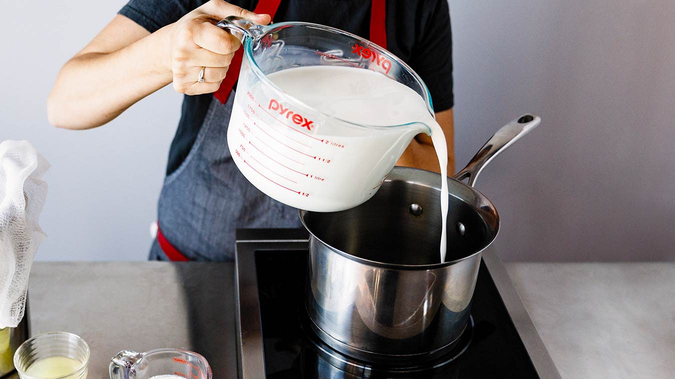 Amoretti Recipe: Homemade Ricotta. Pouring milk and cream in saucepan.