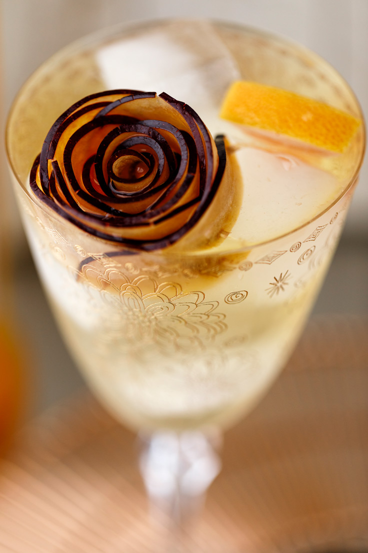A fancy plum garnish on Amoretti Summer Sangria Recipe with stone fruits and citrus
