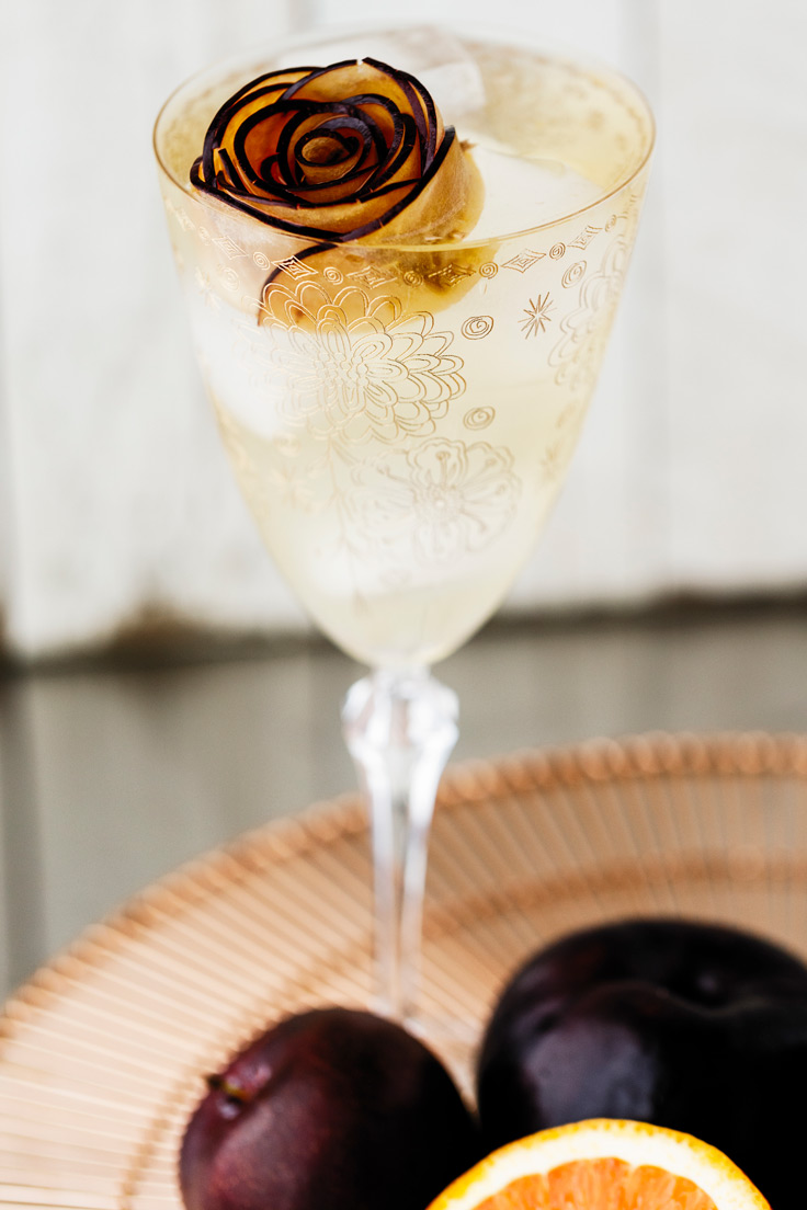 A glass of Amoretti Summer Sangria Recipe with stone fruits and citrus