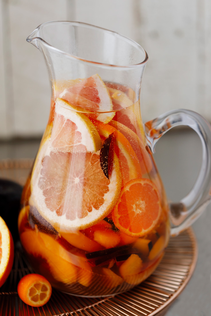 A pitcher of Amoretti Summer Sangria Recipe with stone fruits and citrus