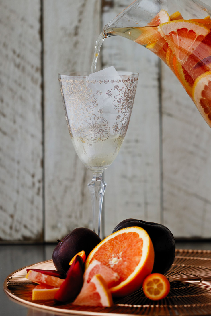 Pour a glass of Amoretti Summer Sangria Recipe with stone fruits and citrus