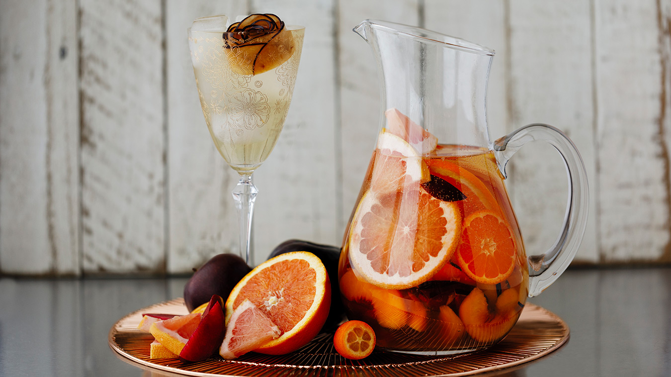 Amoretti Recipe: Summer Sangria with stone fruits and citrus, garnished with a plum rose