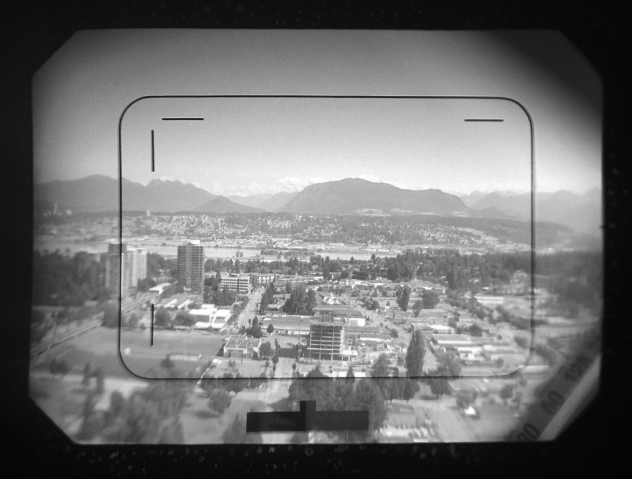 Werramat's viewfinder: frame lines with parallax markings, litght meter indicator (bottom-center) and lens readings (bottom-right). Note that the lens readings are projected via mirrors — it's not an enormous barrel; also, I wasn't able to catch the aperture values with my iPhone here, which are normally visible if you look through (even with glasses on).