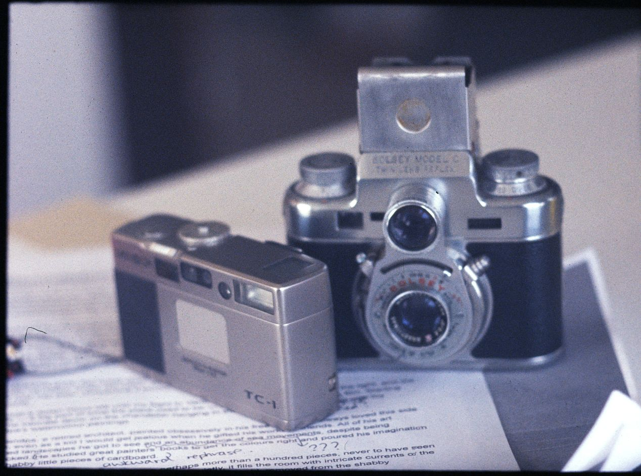 Bolsey Model C is somewhat heavy at 538g/1.2lb, but it's smaller (shorter) than most TLRs. Here, it stands next to one of the smallest 35mm film cameras ever made: Minolta TC-1. Model C certainly isn't pocketable; nevertheless, it's easy to hold in hands — you'll need both — and won't give you a shoulder burn, as some other TLRs may.