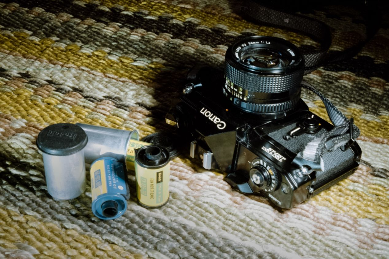 The Canon EF and some refillable 35 mm film cartridges from the days before DX codes. Taken with an Olympus IS-3000 bridge camera on Kodak Color Plus 200 film.
