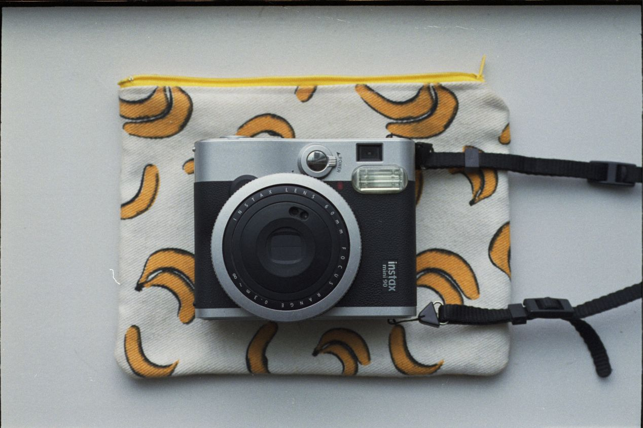 My wife's Instax Mini 90 with a banana cloth pouch we bought in Thailand.