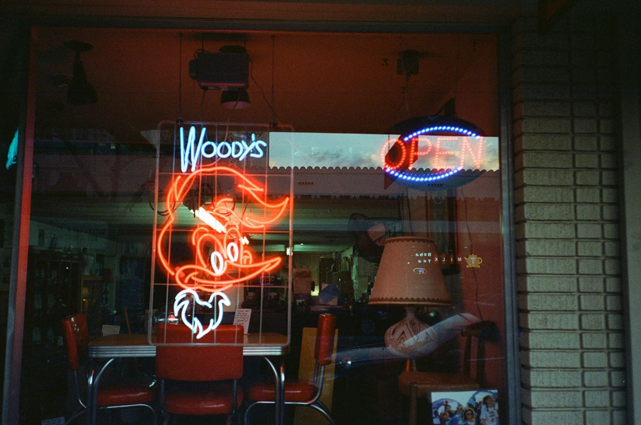 Neon Sign Illuminating the Window of an Antique Shop in Orange County, California. Taken with a Yashica T5 and CineStill 800T film.