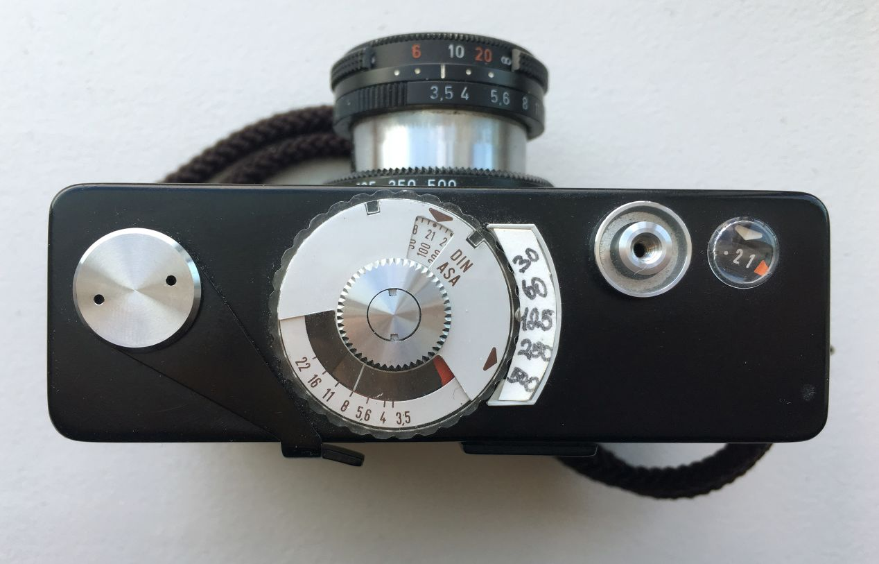 Top view of a Rollei 35B with the lens fully extended. The light meter is set up for an ISO/ASA 100 film via the small metal wheel at the top of the camera/middle of this image. The plastic transparent dial under it is rotated towards the 1/500th shutter speed, which I drew by hand with a pen on a small piece of thin cardboard. The needle shows that the safe aperture to use in these lighting conditions is 𝒇8, which I would have to change from 𝒇3.5, as marked on the lens barrel. You can almost see the shutter speed set to 1/500th as well, partially obstructed by the camera's tiny body. At the tip of the lens, the distance is set to just under 10', and on the left, you can see a counter, pointing to the 21st frame elapsed.