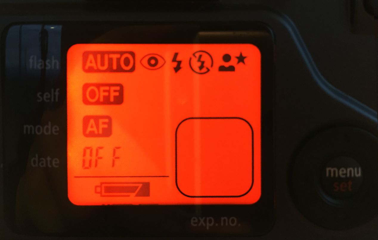 The menu screen turns orange as you cycle through the settings. The rounded square in the bottom-right would typically have an oversize frame number indicator, but in this case, I don't have the film in the camera, so it's empty.