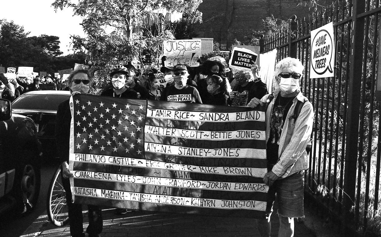 Protesters with the American flag marching to the Boston State House.
