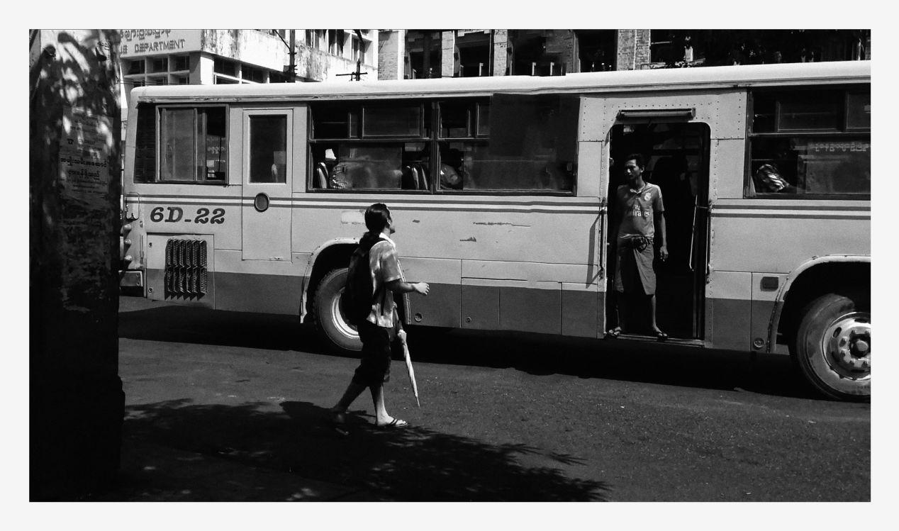 A bus conductor chants, helps passengers aboard. Myanmar, Yangon 2016.
