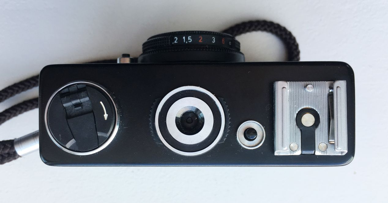 Bottom view of a Rollei 35B. The film rewind knob is on the left, unlocked by pressing the button on the right of the tripod hole. The film cover is unlocked by rotating the two black tabs around the tripod hole counter-clockwise. The hot shoe is on the right. The numbers on the lens barrel are the metre equivalents of the focus distance on the other/top side.