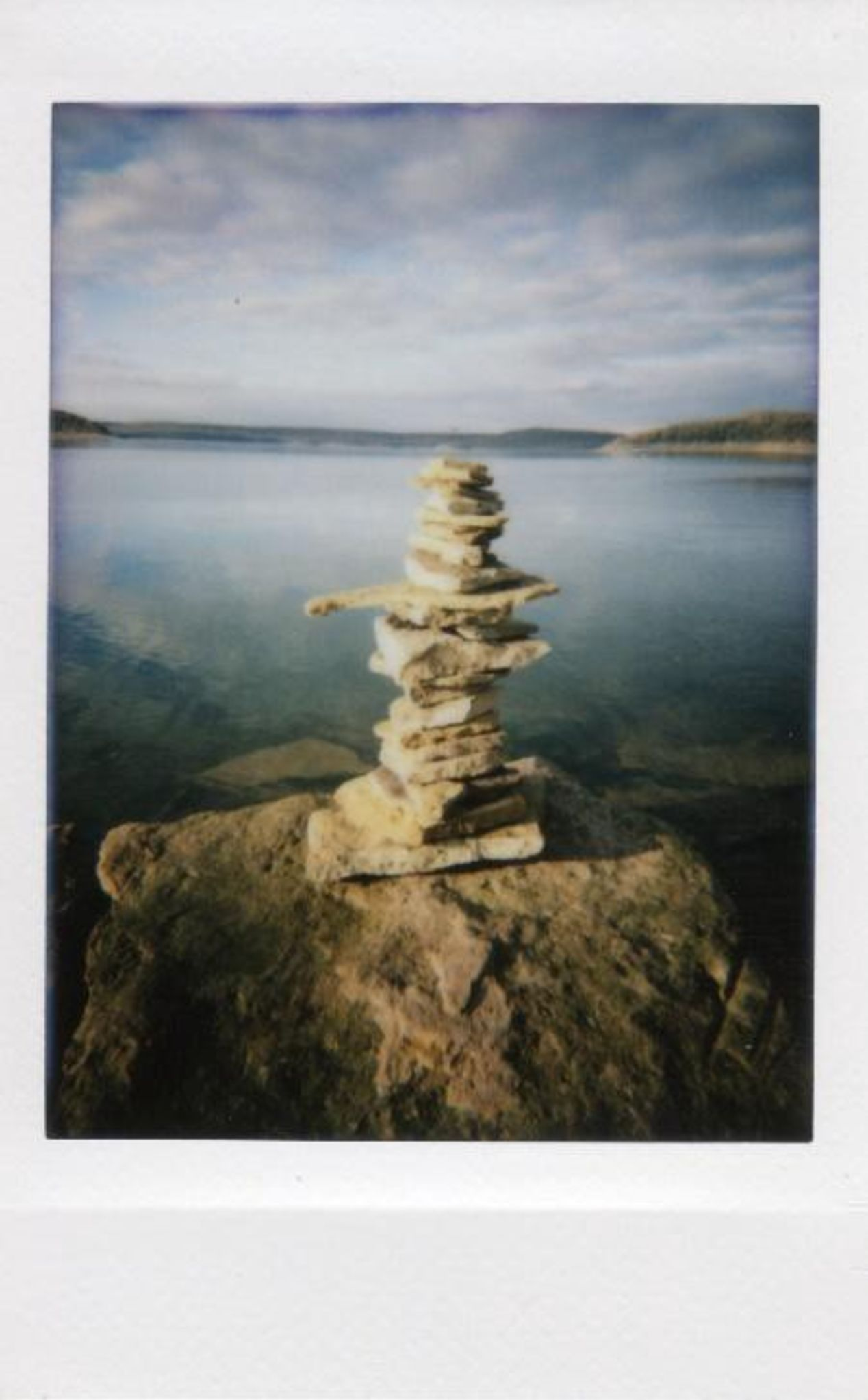 Photo of Lake Tenkiller in Oklahoma of some rocks stacked by the water. Taken with Lomo Instant Mini.