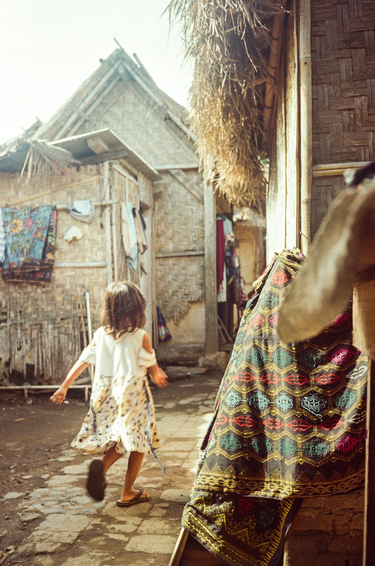 Straw houses, hand-woven cloth, and a happy child. Captured on Kodak ColorPlus 200.