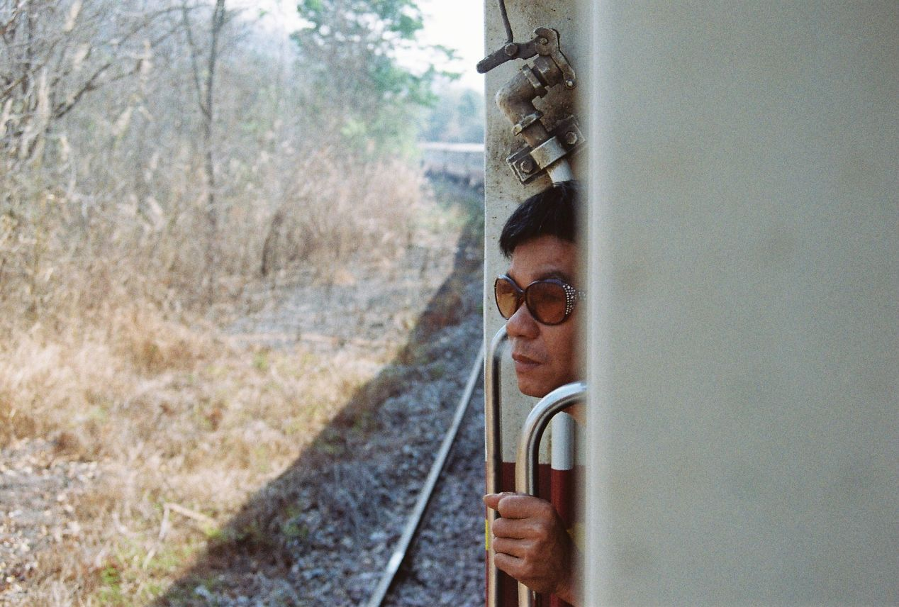 A gentlemen wearing strange shades looking out from the train window as we snail towards Bangkok. Yashica FX3 Super 2000, Color Plus 200.